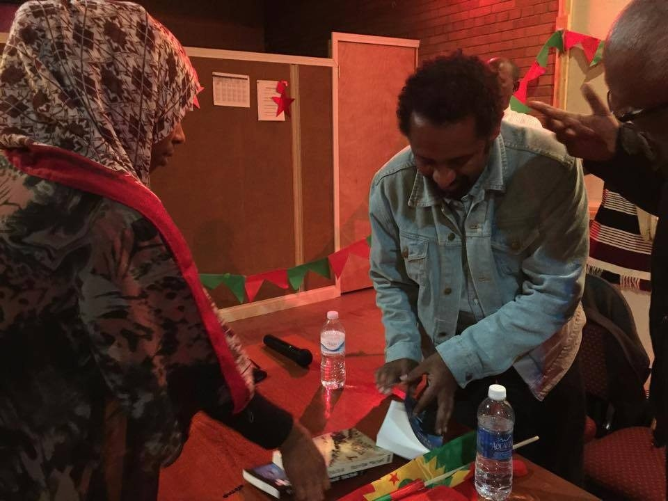Photo - Tesfaye Gebreab signing Ye Jemila Enat book