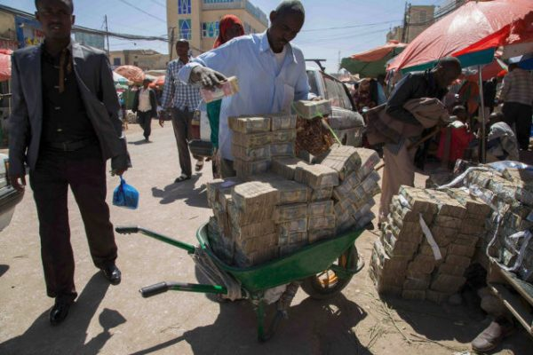 Photo - Foreign currency trader moving a cash pile, Hargeisa, Somaliland